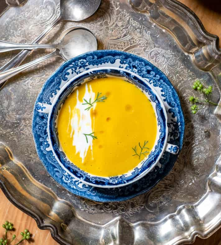 Overhead shot of orange, carrot soup garnished with swirls of sour cream, cilantro leaves and oil - in a blue and white transferware bowl on a silver tray.