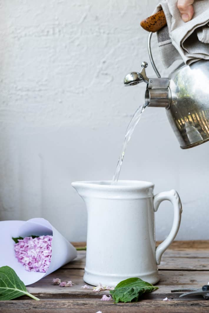 Hot water being poured from a kettle into an ironstone jug with a hydrangea laid to the side.
