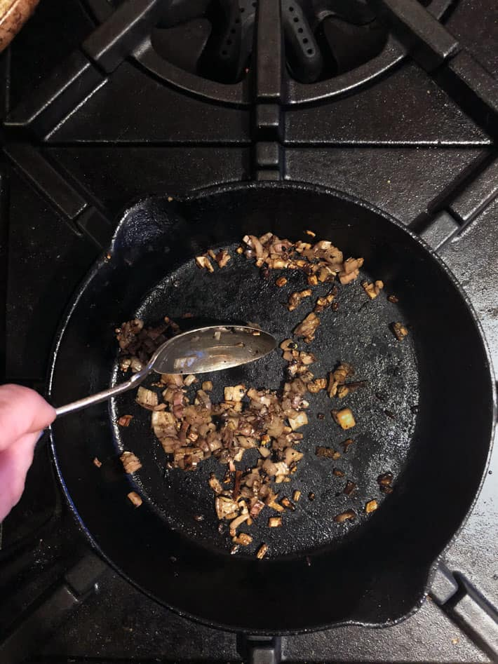 Sautéing minced shallots in steak drippings in cast iron pan.