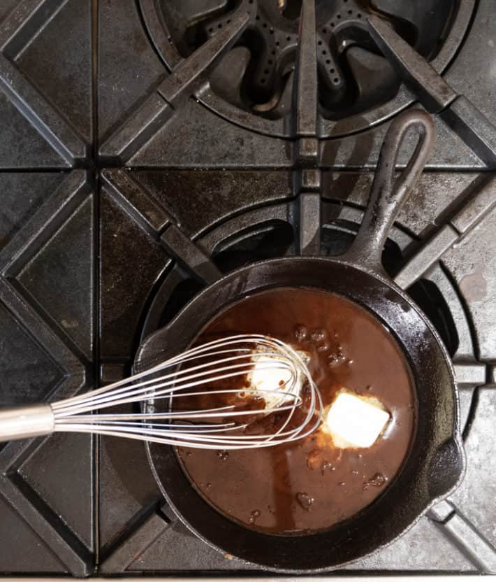 Whisking butter into a pan sauce being made in a cast iron skillet.