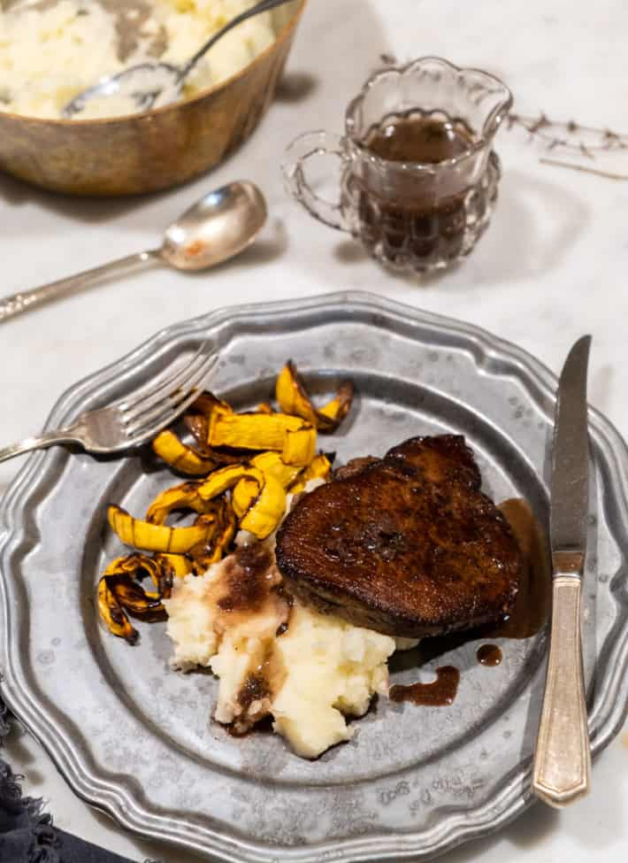 A pewter plate served with mashed potatoes, sliced squash and a tenderloin steak with pan sauce drizzled over it.