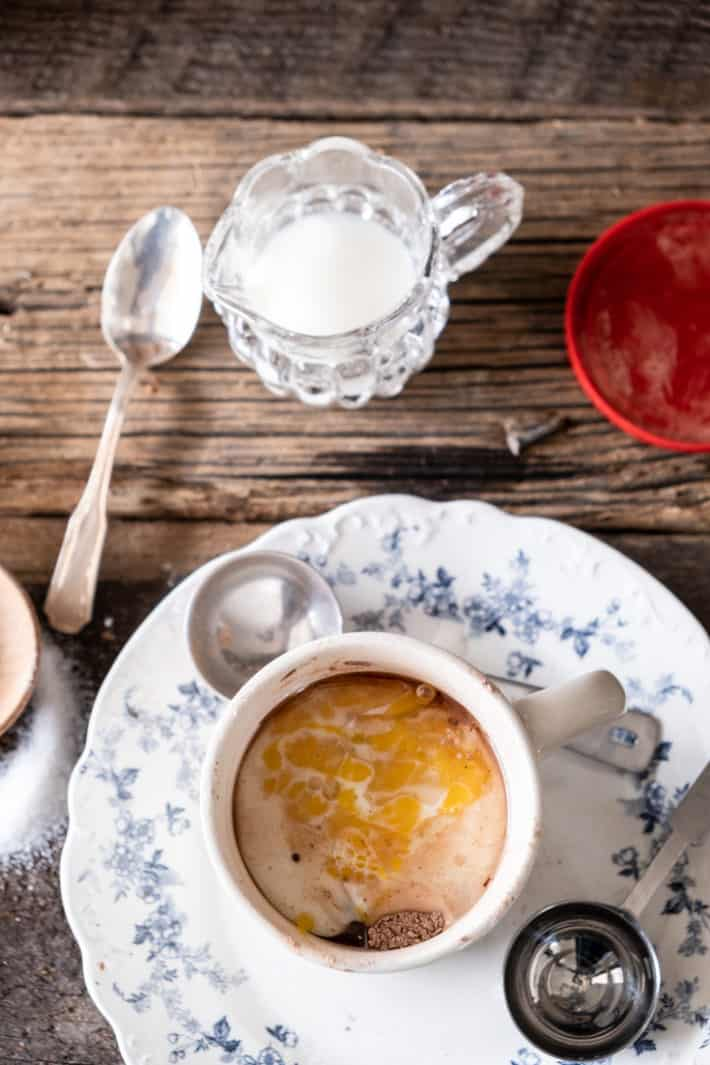 Wet ingredients of cake in a cup in ironstone mug on a vintage blue and white plate set on wood tabletop.
