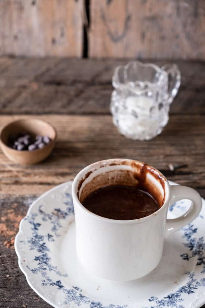 Ironstone mug filled with chocolatey looking batter set on wood table with a small pitcher of milk in the background.