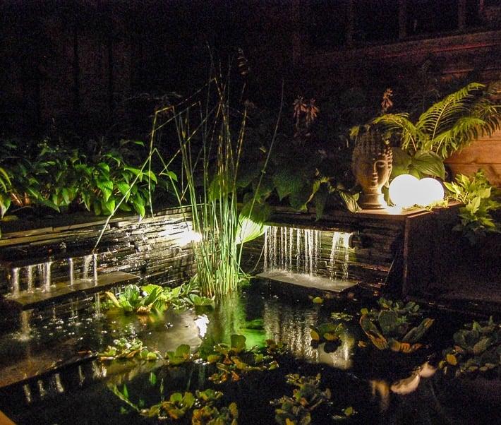 Glowing outdoor orbs in garden above lit up waterfall in backyard pond.