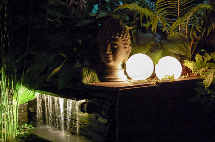 DIY glowing outdoor orbs for backyard behind Buddha head and pond waterfall.