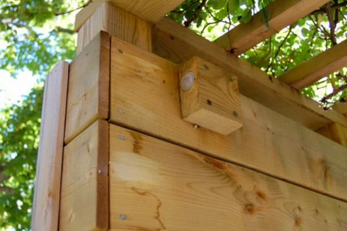 Block of wood screwed into top of arbour to act as a striker for an invisible gate latch.