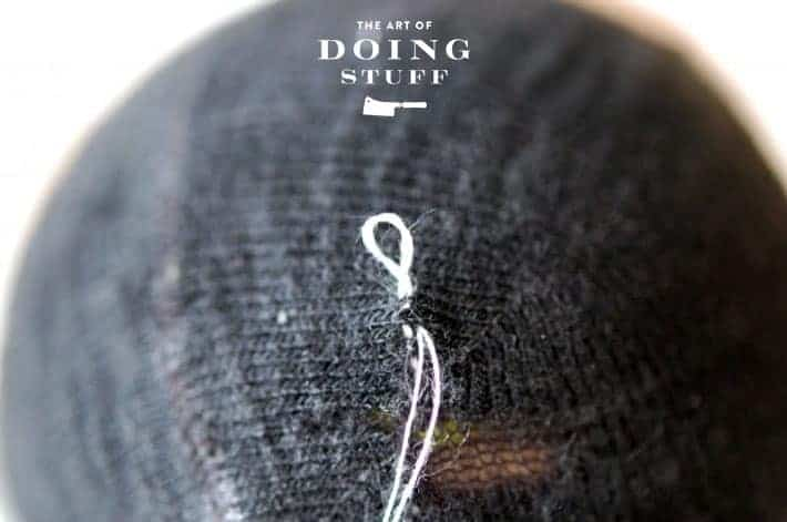 Black sock with white thread sewing it up.