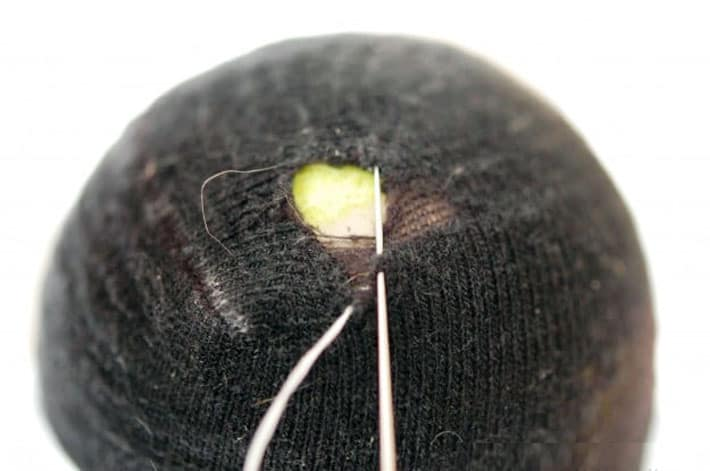 Black sock over yellow tennis ball being darned with white thread.