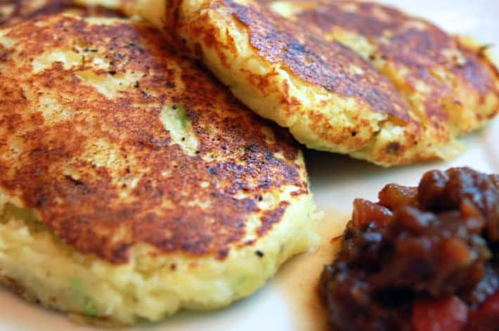 Close up shot of potato pancakes served with chutney style sauce.