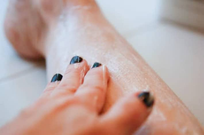 Hand rubbing hair conditioner into leg as a shaving cream alternative.