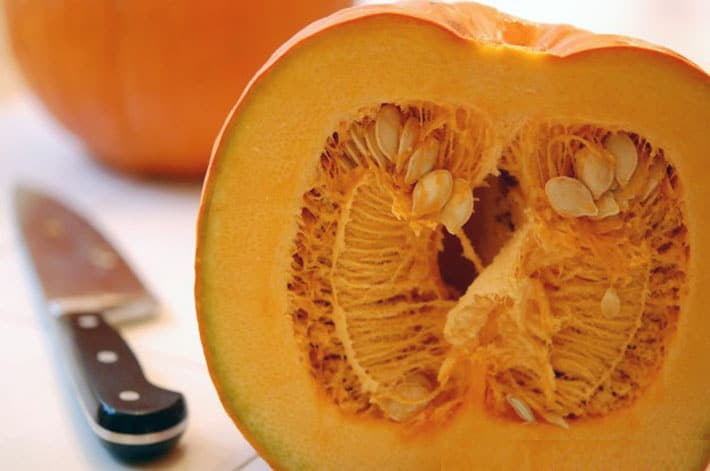 Pie pumpkin cut in half showing all the seeds and fibres on a white counter with knife in the background.