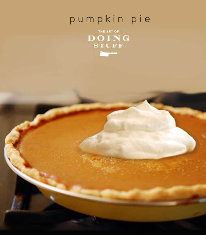Cooked pumpkin pie in vintage enamel pie plate, topped with maple syrup whipped cream.