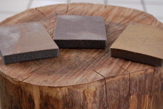 3 sand paper blocks sit on top of a tree stump.