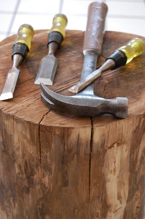An array of chisels and a hammer sit on top of a debarked tree stump.