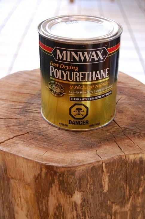 A small can of Minwax Plyurethane in clear satin, sits on a tree stump.