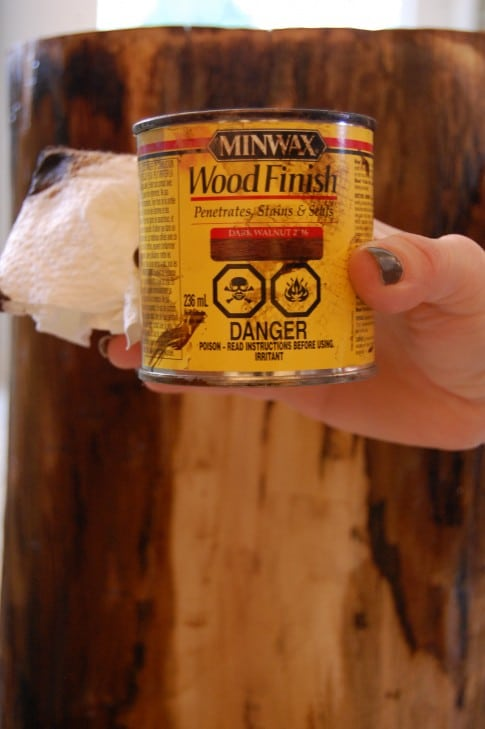 A woman's hand holds up a small can of Minwax wood finish with a yellow label.