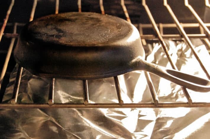 Cast iron pan upside down on oven rack with tin foil underneath.