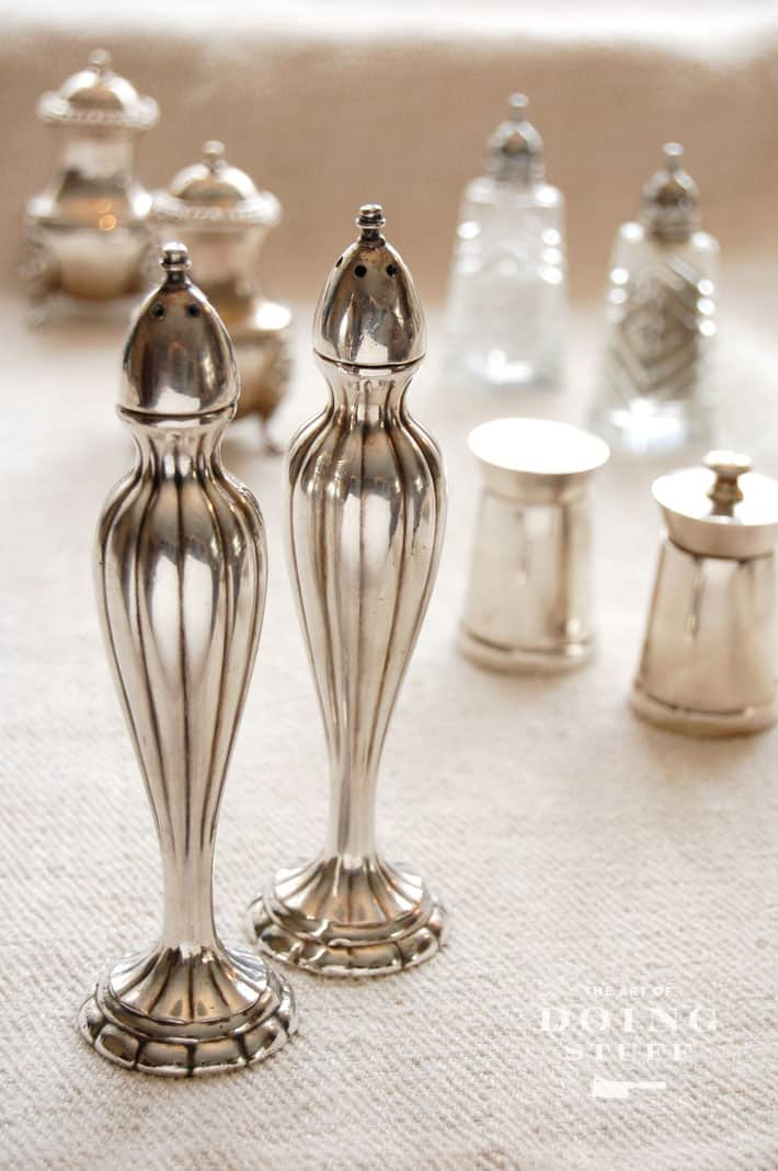 Tall, slender antique silverplate salt and pepper shakers on natural linen tablecloth, various other vintages shakers in background.