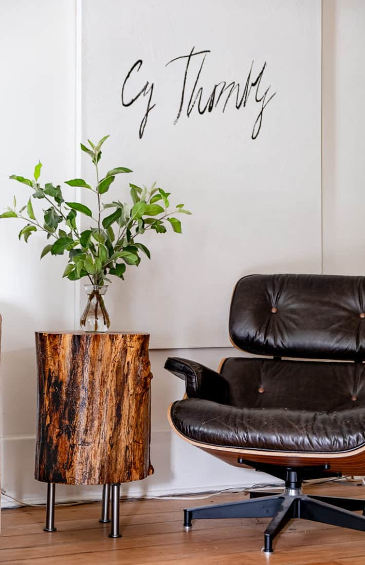 DIY tree stump table sits beside classic Eames chair in white room.
