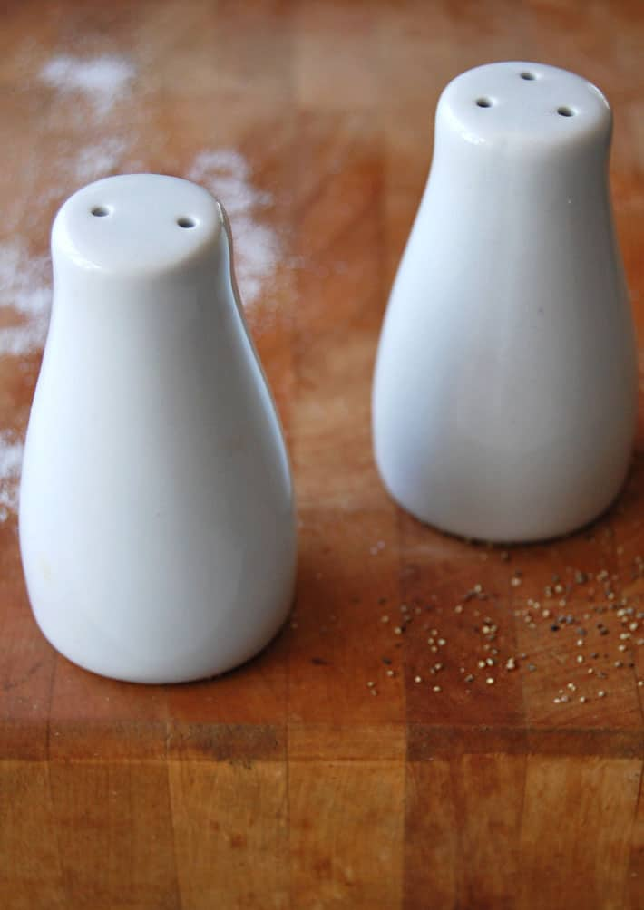 Contemporary, white, sleek ceramic salt and pepper shakers.