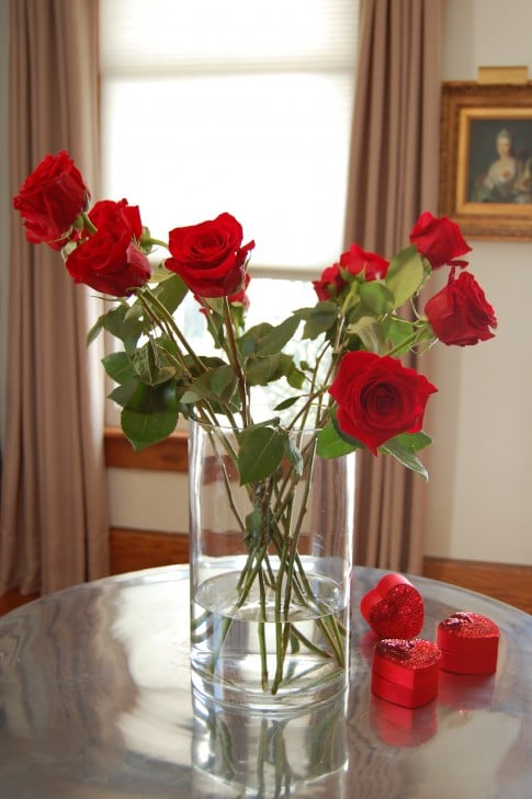 A dozen red roses in a clear vase, that's too big for them. Roses are flopping and bland looking.