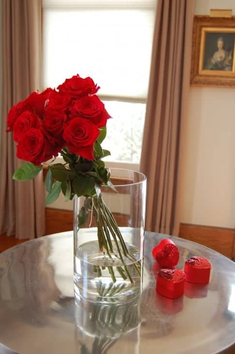 Contemporary arrangement of a dozen red roses in a glass cylinder vase on a stainless steel round table.