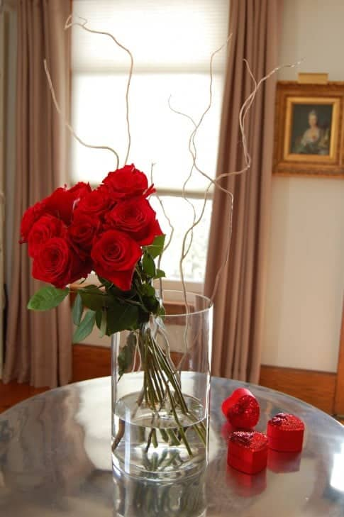 Contemporary arrangement of a dozen red roses tied together in a bunch, leaning to the side in a clear cylinder vase with a few white curly branches for interest.