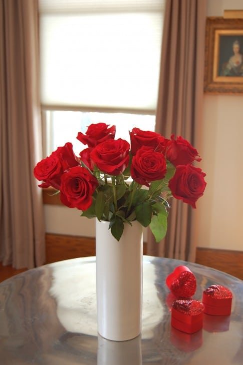 A dozen red roses in a white, narrow cylinder vase. Shows off how a smaller vase mouth helps to keep roses upright and in place.