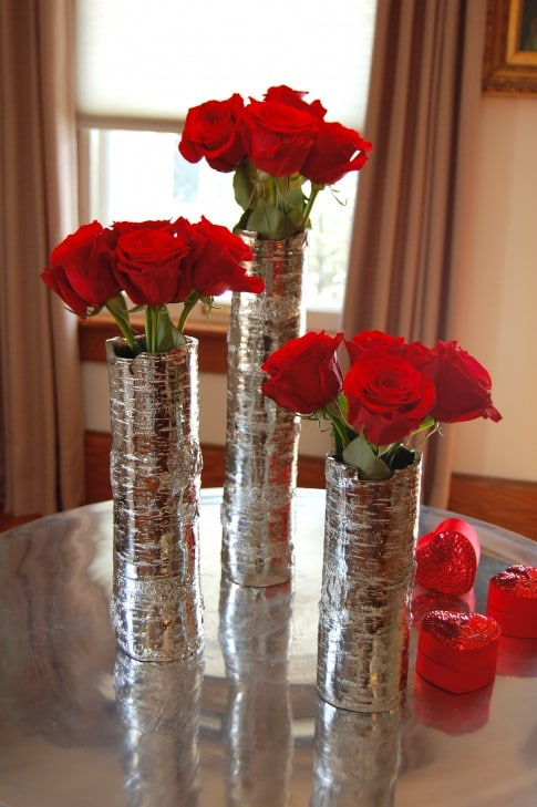 A dozen red roses divided among 3 narrow silver cylinder vases, with 4 roses in each vase.