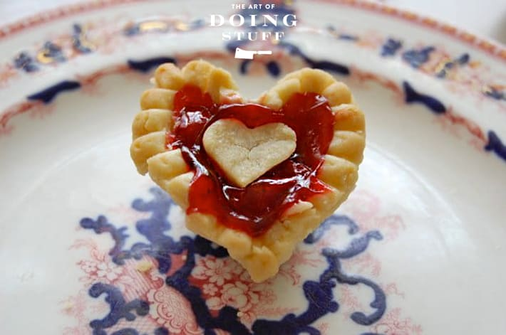 Mini cherry tart in the shape of a heart on antique flow blue plate.