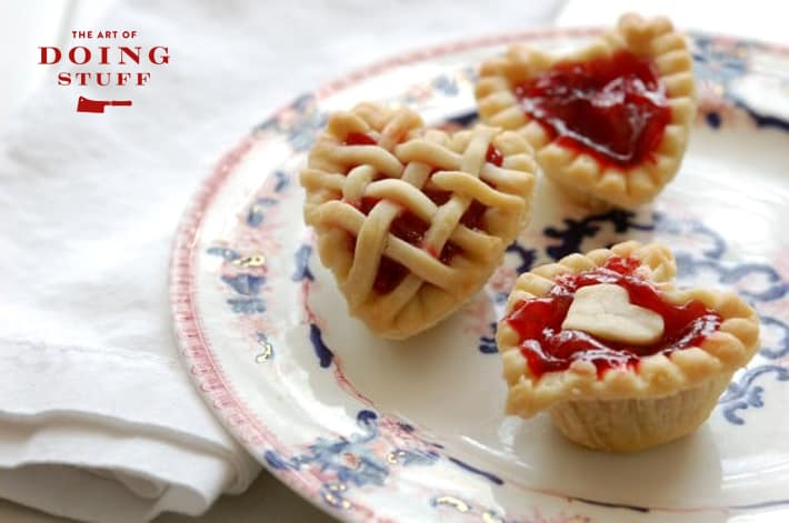 Beautiful cooked mini cherry tarts in the shape of hearts on an antique flow blue plate with white napkin.