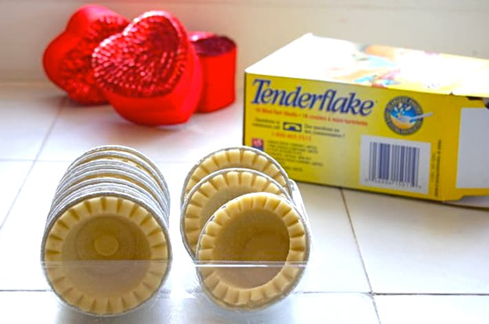 Frozen mini tart shells on a white tile counter with empty cardboard box and red sequin hearts.