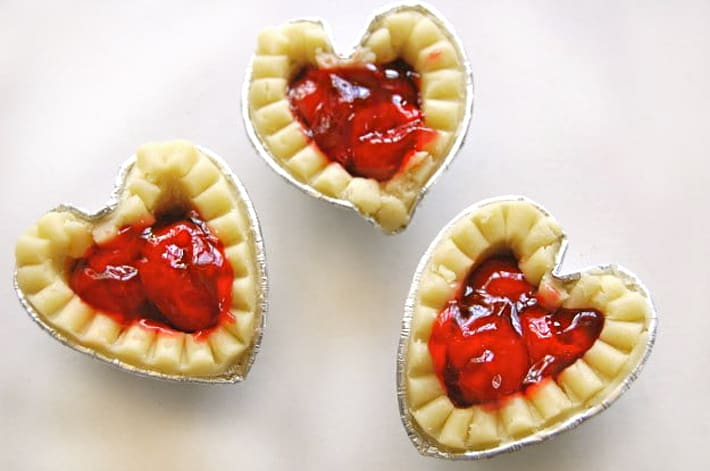 Mini frozen tart shells filled with cherry pie filling on white counter.