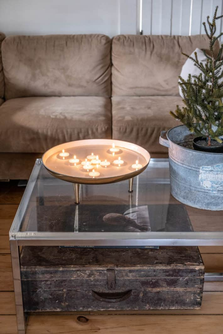 DIY floating tea lights in a modern bowl on a clear glass coffee table with rustic accents around.