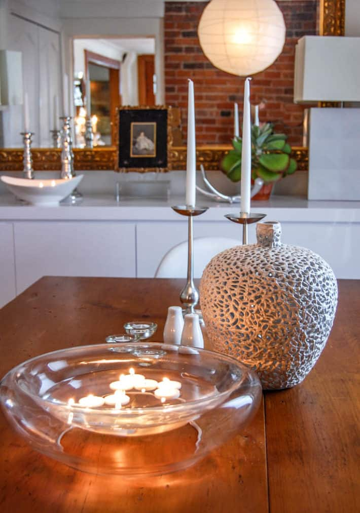 Floating tea lights in modern clear glass bowl on rustic harvest table.