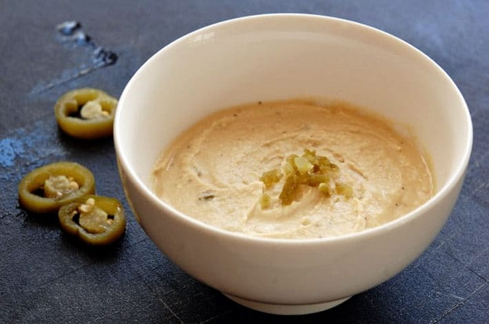 Jalapeno hummus in a white bowl on a black counter.  Sliced jalapenos to the side.