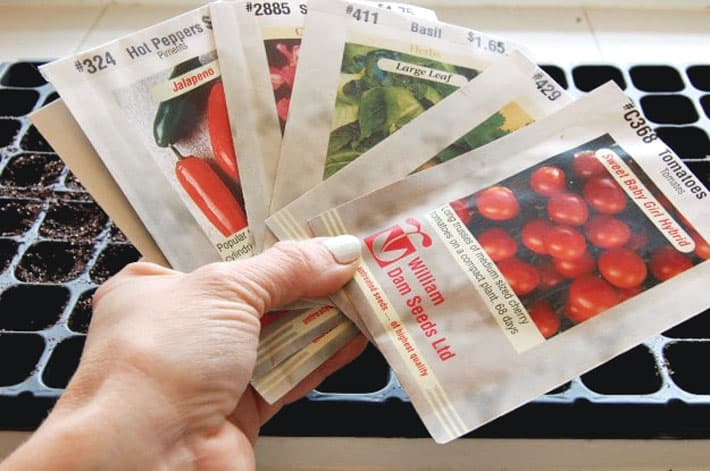 An array of seed packets held over a seed tray ready for planting.