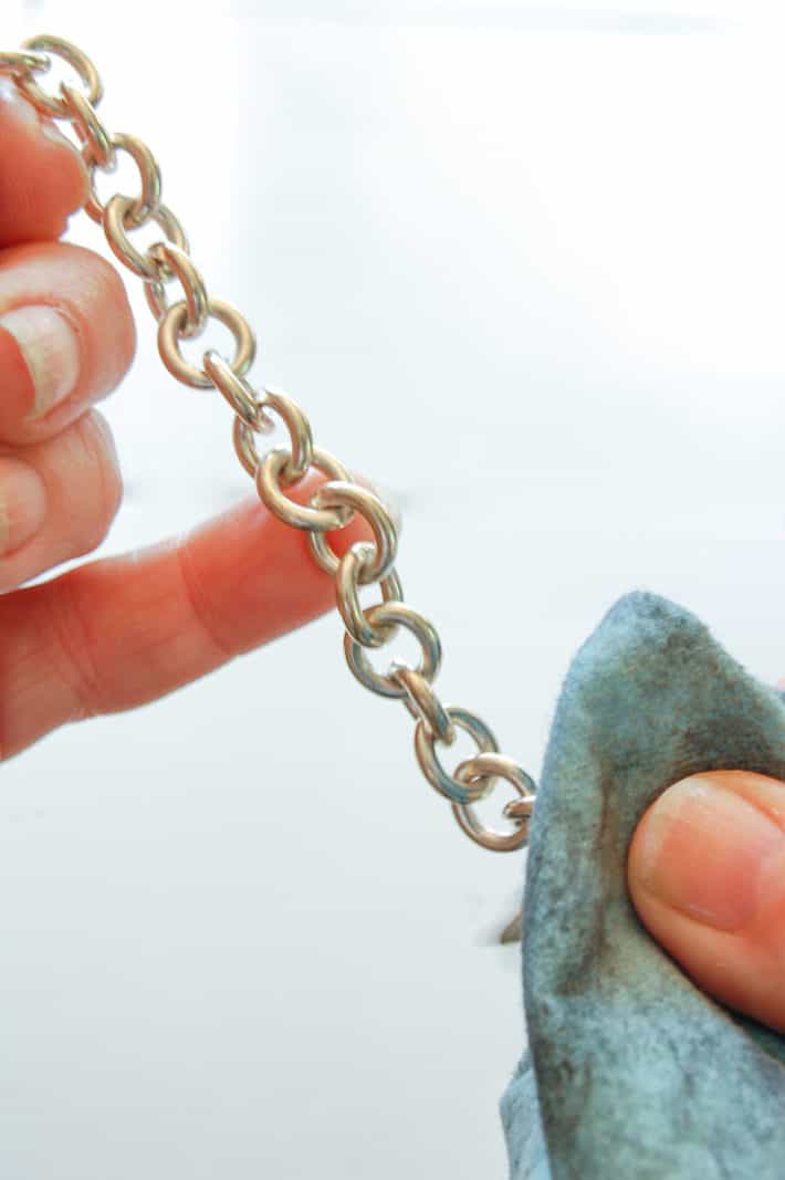 Cleaning sterling silver chain with polishing cloth.