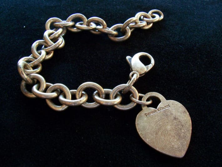 Before picture of silver bracelet with heart charm prior to cleaning in silver dip.