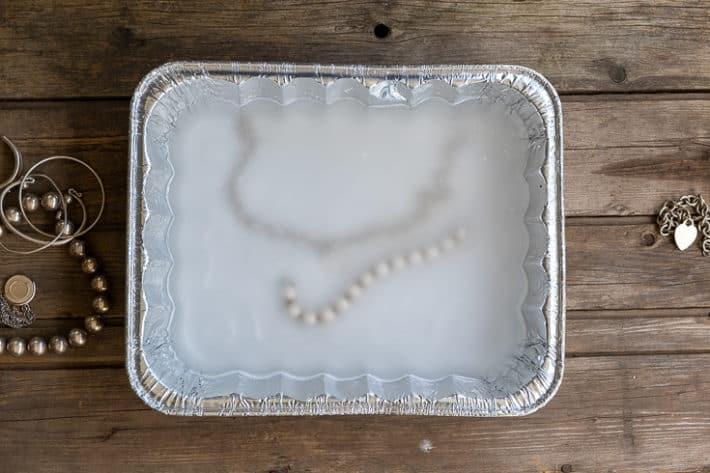 An aluminum pan with silver jewelry, hot water and sodium carbonate in it for cleaning tarnished metal.