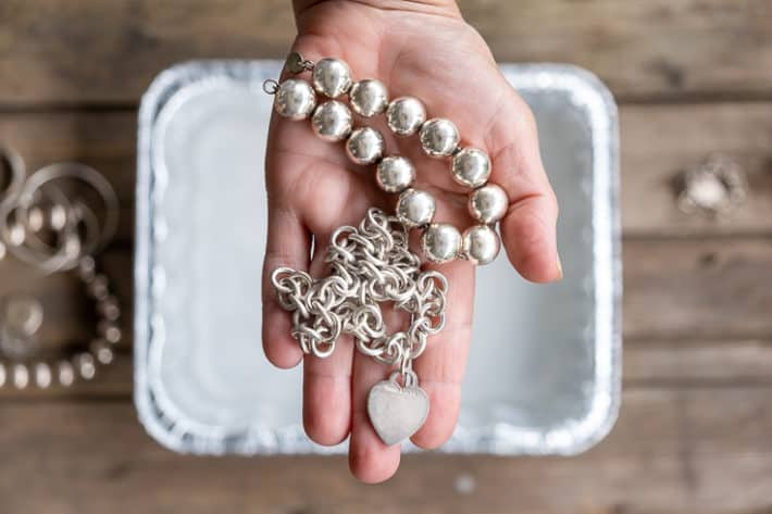 A woman's hand holds out a silver Tiffany heart necklace and silver bead necklace after being cleaned.