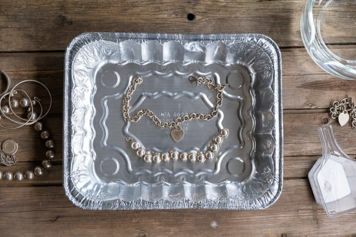 Two silver necklaces placed inside a common aluminum pan on a wood table.