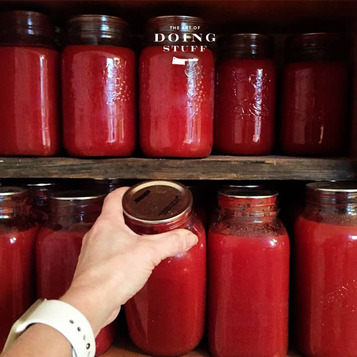 Rows of large mason jars filled with tomato sauce on rustic barn board shelves.