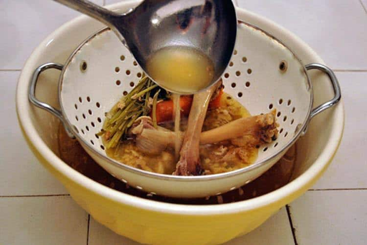 chicken bone filled colander over bright yellow bowl on white countertop.