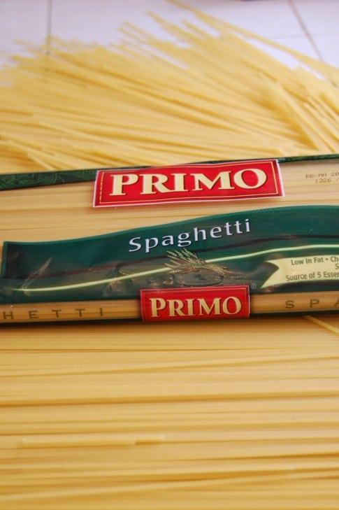 Cellophane package of spaghetti sitting on loose uncooked spaghetti on a white countertop.