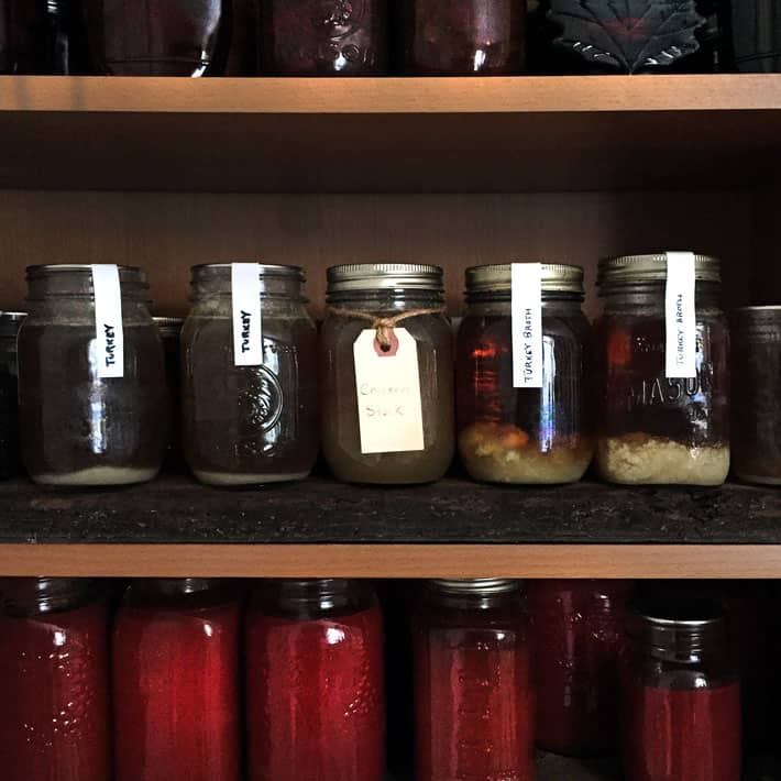 Wood pantry shelves filled with red tomato sauce on the bottom shelf, chicken broth on the middle shelf and maple syrup on the top shelf.