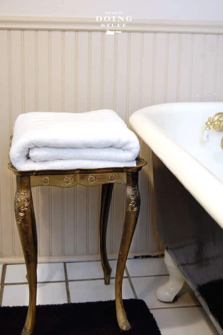 Fluffy white folded towel on a gold florentine table beside a clawfoot bathrub.