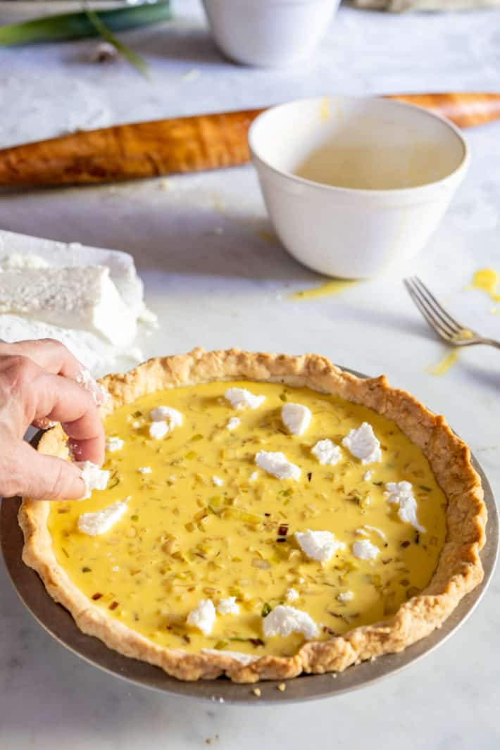 A leek quiche being topped with crumbled goat cheese with other ingredients in the background.