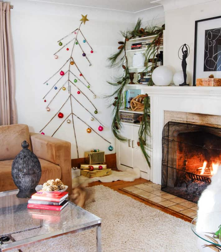 Twig tree with vintage glass ornaments on a white wall in a living room with a roaring fire.
