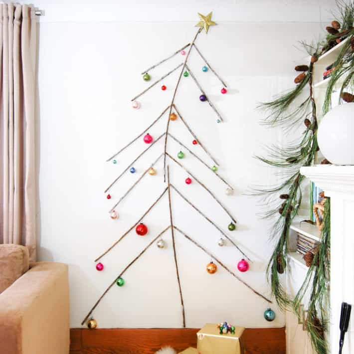 A tree made of twigs, flat against a wall from floor to ceiling complete with ornaments.